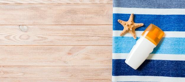 日焼け止めのボトル、縞模様の青いタオル、木製の背景に貝殻。夏の旅行のコンセプト。コピースペースのある上面図。