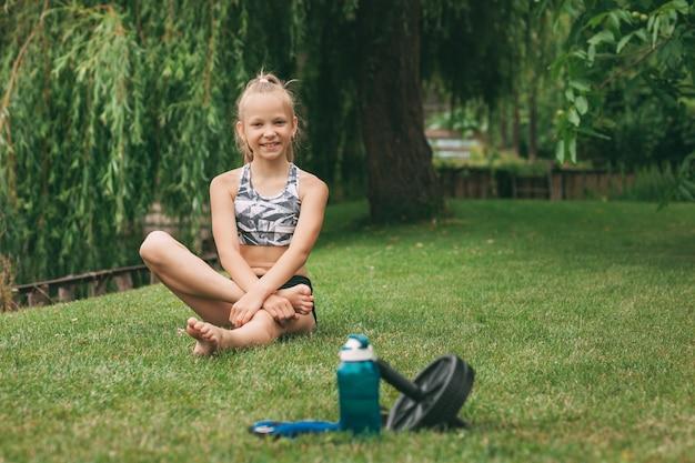 Бутылка воды, колесо для спорта, гири и девушка, отдыхающая после завершения онлайн-тренировки.