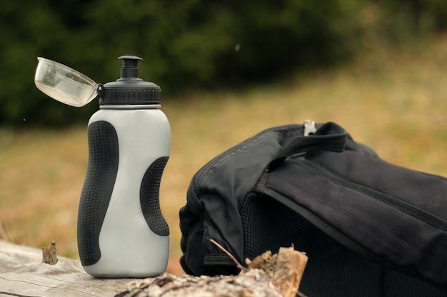 잔디에 물 한 병과 배낭. 캠페인에서 레크리에이션의 개념.