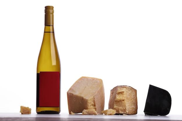 白ワイン、高価なチーズ、かび臭いチーズ、黒チーズのボトル。白い背景に。ロゴの場所。