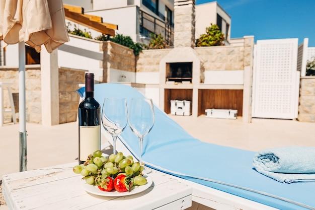 우산 그늘에서 선베드 근처 해변에서 와인 두 잔과 과일 한 병