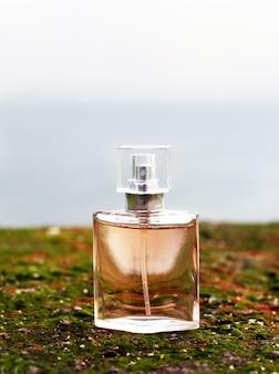 海を背景に緑の苔の上に女性の香水のボトルが立っています。海の夏のフェミニンな香り。自然