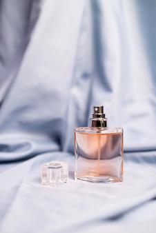 シルクの織り目加工の生地に女性の香りのよい香水のボトル Premium写真