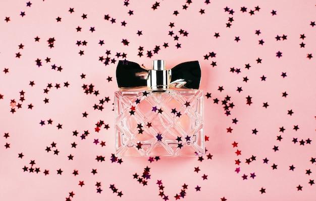 マルチカラーの輝きと紙吹雪とお祝いのピンクの背景に女性の香水のボトル。上からの眺め。休日の概念2月14日または3月8日。