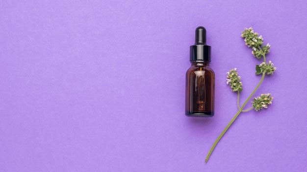 Бутылка с пипеткой и веточкой лекарственной травы на фиолетовом фоне. место для текста. плоская планировка.
