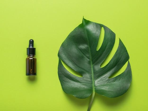 Бутылка с пипеткой и листом монстеры на зеленом фоне. плоская планировка.