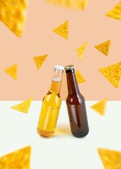 デュアルカラーベージュの背景にクラフトラガーとポータービールのボトル。フローティング、フライング、浮揚ナチョススナック。世界ビールの日またはオクトーバーフェストのコンセプト。モダンな写真のミニマルな色
