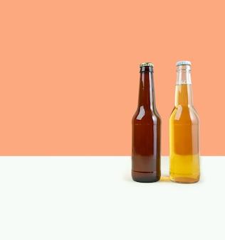 デュアルカラーベージュの背景にクラフトラガーとポータービールのボトル。世界ビールの日またはオクトーバーフェストのコンセプト。写真のミニマルな色。正面図。スペースをコピーします。水平。