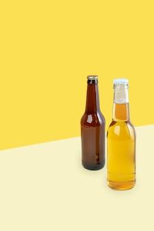 デュアルカラーの黄色の背景にクラフトラガーとポータービールのボトル。世界ビールの日またはオクトーバーフェストのコンセプト。写真のミニマルな色。コピースペース。等角対角投影。