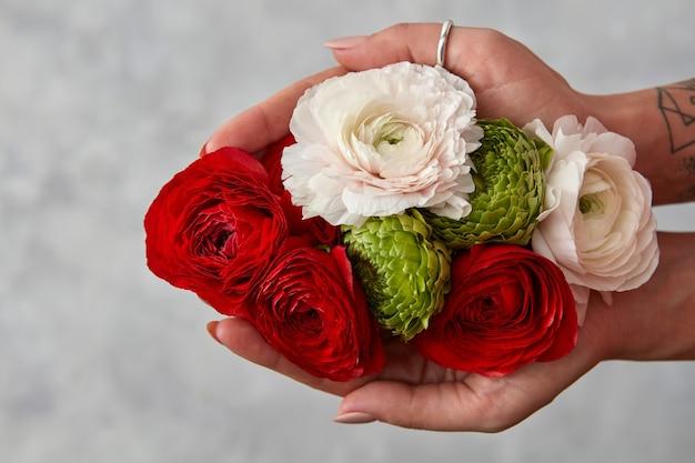 꽃다발 다채로운 꽃 회색 배경에 여자를 잡고 있다. 축제 인사말 카드의 개념은 발렌타인 데이입니다.