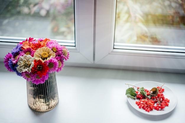 창턱에 guelder 장미 열매와 가을 꽃의 꽃다발