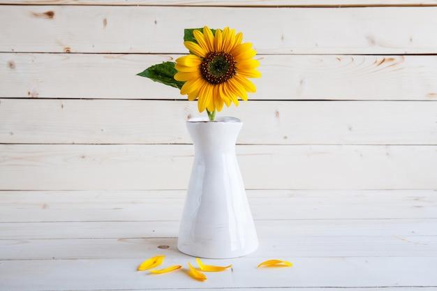 汚れた木製のテーブルの上に花瓶に秋のひまわりの花束。そして