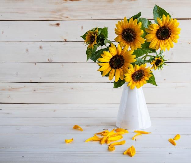 汚れた木製のテーブルの上に花瓶に秋のひまわりの花束。