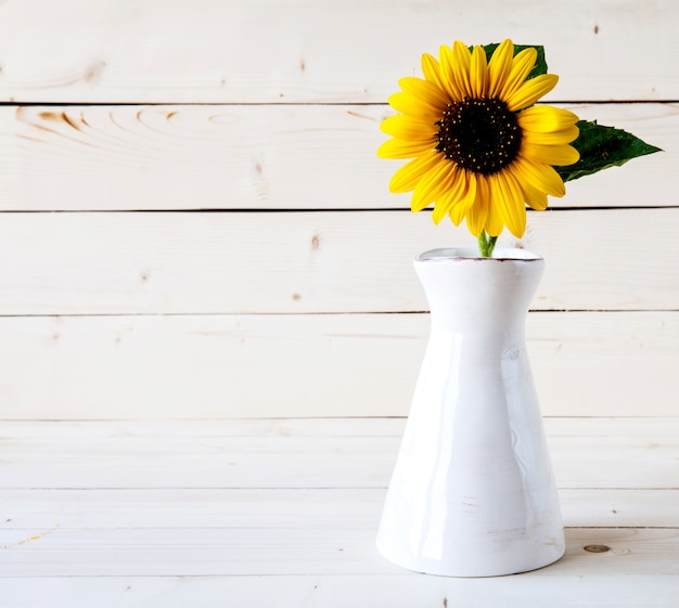 Букет осенних подсолнухов в вазе на шероховатом деревянном столе.
