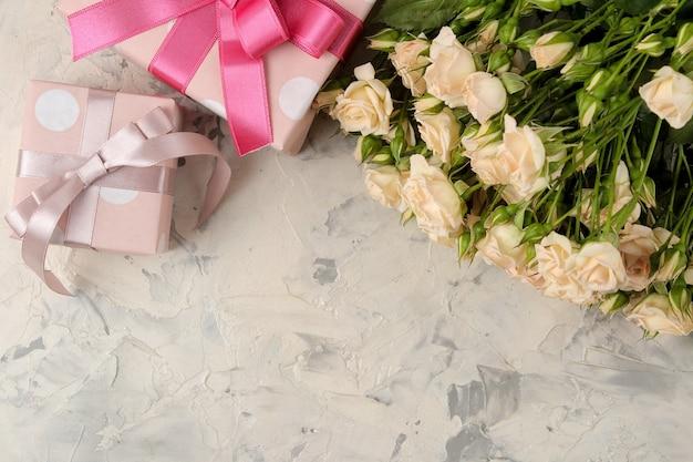 밝은 콘크리트 표면에 아름다운 부드러운 미니 장미 꽃다발과 선물 상자