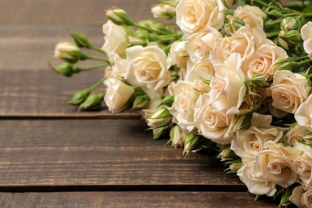 テキストのためのスペースと茶色の木製のテーブルの上の美しい柔らかいミニバラの花束