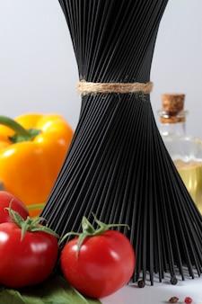 イタリア料理の材料を組み合わせた黒いスパゲッティの花束