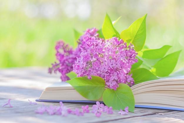 정원의 테이블에 펼쳐진 책의 페이지에 피는 라일락 꽃다발