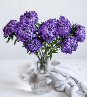Букет из синих хризантем в стеклянной вазе и вязаный элемент на белом фоне.