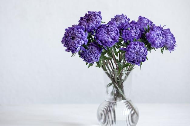 白い背景、コピースペースのガラスの花瓶に青い菊の花束。