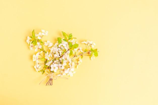 テキストの場所と黄色の背景に咲く桜の枝の花束。フラットレイ、はがき、バナー、コピースペースは空白。上面図、垂直