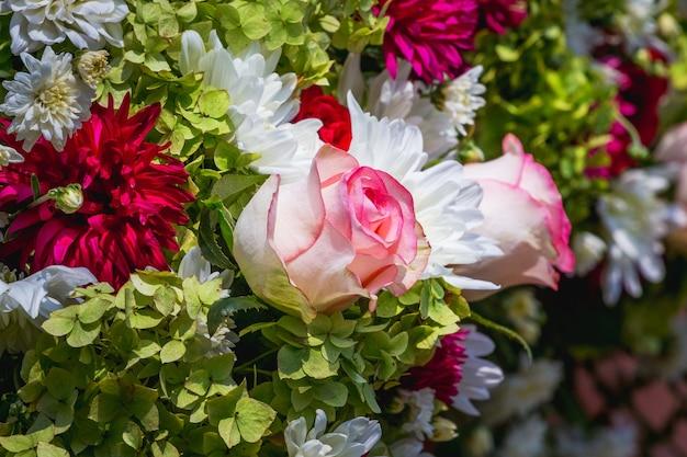 真ん中にピンクのバラが咲く鮮やかな花の花束_