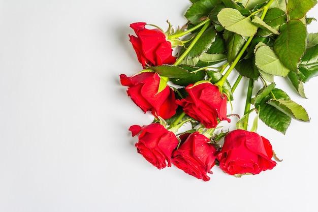 白い表面に分離された真っ赤なバラの花束