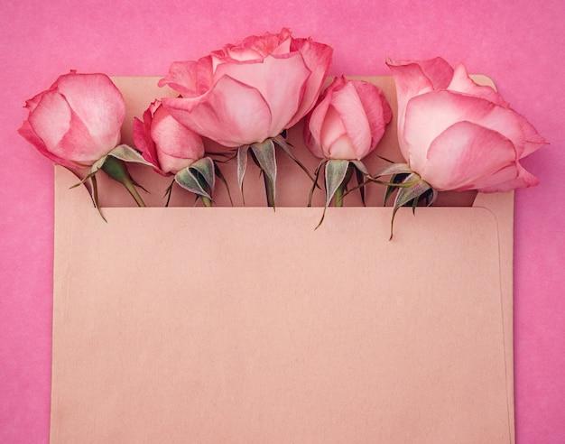 ピンクの背景の封筒に明るいバラの花束。デザインの場所が書かれたはがき。