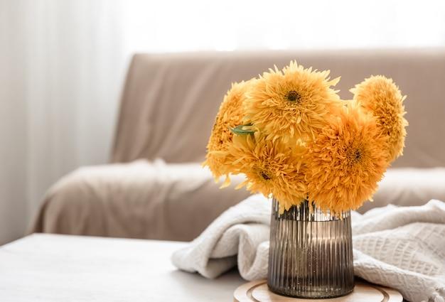 방 내부의 흐릿한 배경에 있는 유리 꽃병에 있는 밝은 해바라기 꽃다발, 복사 공간.