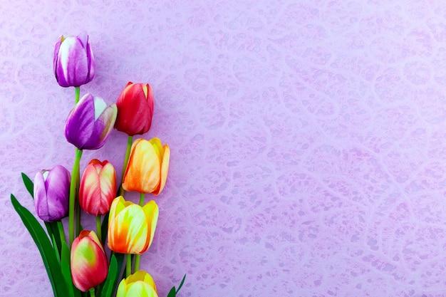 紫色の紙の背景にカラフルなチューリップの花束春のフラワーアレンジメントの背景。