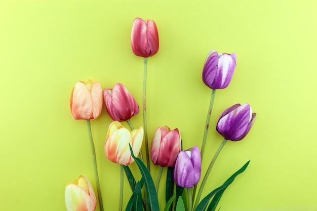 黄色い紙の背景にカラフルなチューリップの花束春のフラワーアレンジメントの背景。