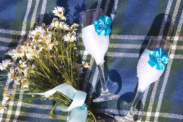 ツイードブルーのベッドカバーまたはシャツにデイジーとウェディンググラスのブーケ。夏の花のロマンチックな背景。テキスト用のスペース。ロマンチックなデート、ピクニック、記念日のお祝いのアイデア。