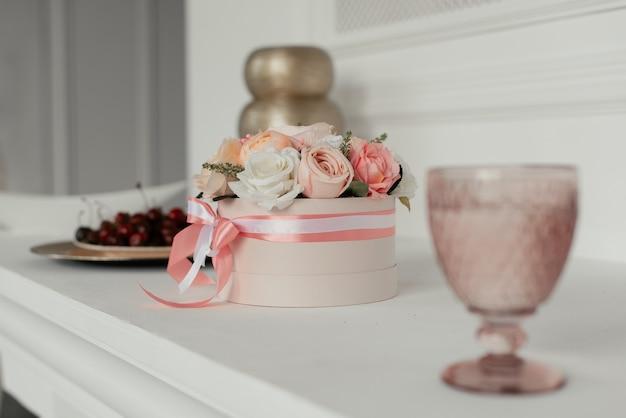 ピンクのガラスの横にある丸いピンクのボックスに装飾的な花の花束