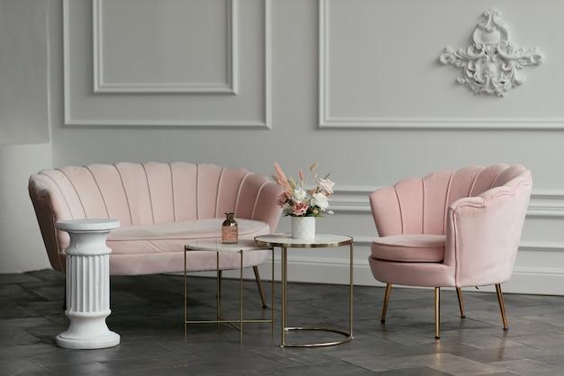 スタイリッシュなピンクの家具を背景に白い花瓶に飾られた花の花束