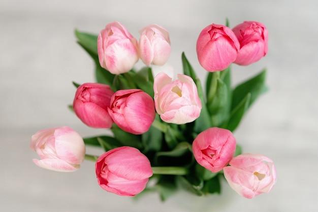 Букет нежных розовых тюльпанов к празднику. день матери, день рождения, день влюбленных. открытка. мягкий выборочный фокус, вид сверху.