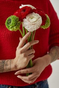 빨간 니트 스웨터를 입은 소녀와 손에 문신이 있는 다양한 꽃의 꽃다발. 발렌타인 데이. 어머니의 날.