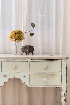 レトロなスタイルの家具に置かれたドライフラワーとヴィンテージジュエリーボックスの花束