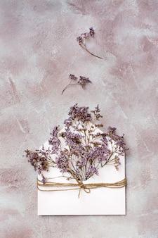 Букет засушенных цветов в светлом конверте, перевязанном веревкой на фактурном фоне. поздравительная романтическая открытка. вид сверху и вертикальный