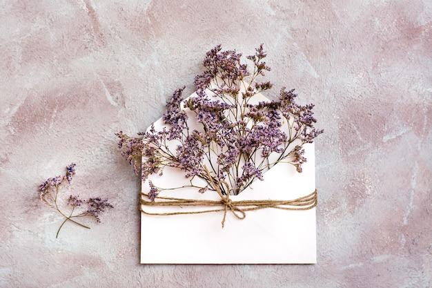 Букет засушенных цветов в светлом конверте, перевязанном веревкой на фактурном фоне. поздравительная романтическая открытка. вид сверху