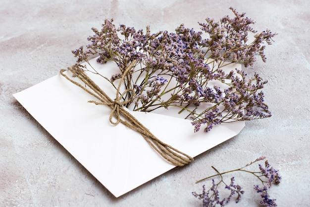 Букет засушенных цветов в светлом конверте, перевязанном веревкой на фактурном фоне. поздравительная романтическая открытка