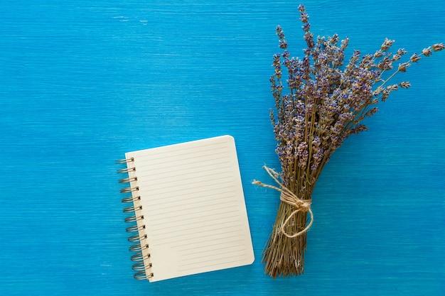 마른 라벤더와 blaknot의 꽃다발은 나무 블루 보드에 놓여 있습니다