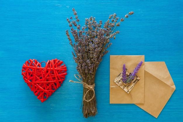 마른 라벤더 꽃다발과 봉투는 나무 블루 보드에 놓여 있습니다