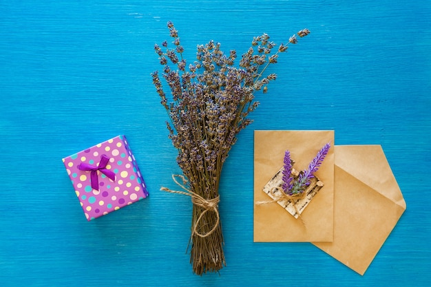 Букет сухой лаванды и конверты лежат на деревянной синей доске.