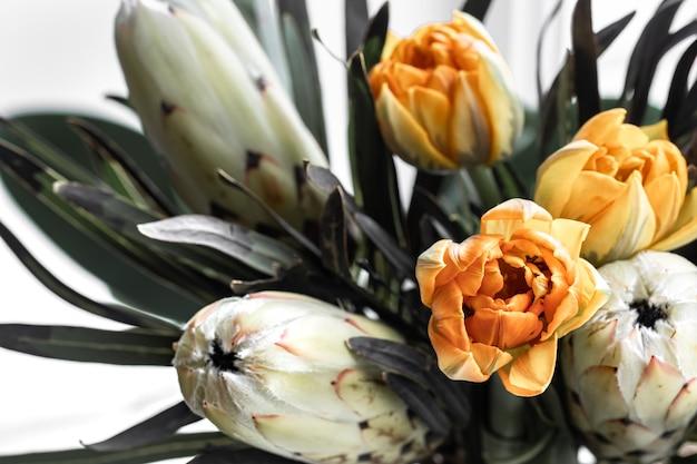 왕실 프로 테아와 밝은 튤립의 이국적인 꽃의 꽃다발. 꽃 조성의 열대 식물.