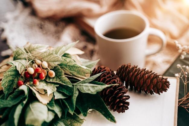 떨어진 가을 노란 꽃다발은 흐릿한 차 한 잔을 남기고 전나무 콘이 따뜻한 음료를 데우는 책과 함께...