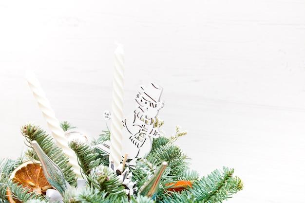 Букет из еловых веток, усиленных снеговиком, елочными игрушками, сушеными апельсинами и белыми свечами. новогодний букет, копия места, светлый фон