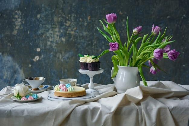 테이블에 꽃, 케이크, 컵 케이크와 차 한 잔의 꽃다발