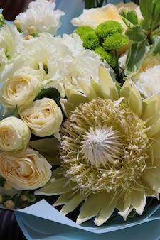 大きなエキゾチックなプロテア牡丹のバラ、白いユーストマ、緑の菊の花の花束