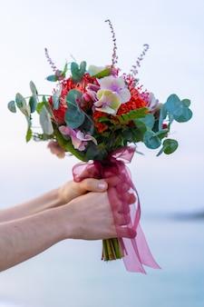 美しい色の結婚式の花の花束。地平線上の海