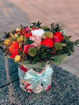 멘톨 활이 있는 상자에 있는 국화, 유스토마, 장미 꽃다발.